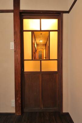 改修後の廊下   玄関ホールとの間の建具はオーナーが自らアンティーク店で見つけた電話BOX用のもの。
