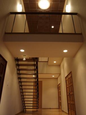 階段室改修後 階段を緩勾配にするにはアプローチが長くなるため、上り勝手を正反対に変えて距離を稼いだ。 また、そのアプローチのために出来たブリッジはホール空間のアクセントとなりストリップ階段と相まって玄関を演出している。