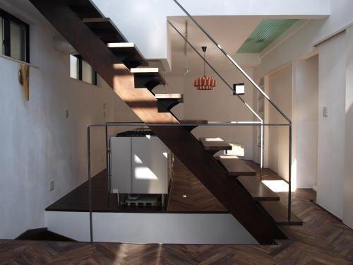 LDK    生活の場は2階に集約、一番奥におよそ3帖の寝室があるロフトへの階段手摺はスチールの黒皮仕上、製鉄過程に発色する素地色が床や壁面にマッチしている